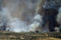 Volo degli aerei con l'aumento bianco denso del fumo dall'incendio violento infuriantesi Immagine Stock