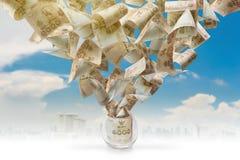 Volo dei soldi dal vetro nel cielo blu Immagini Stock