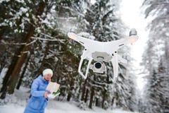 Volo del fuco alla foresta nevosa di inverno pilotata dalla giovane donna fotografie stock
