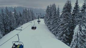 Volo del fuco di snowboard e dello sci di inverno in ski-lift delle montagne sopra l'elevatore e la gente stock footage