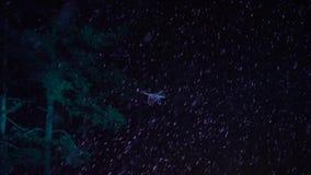 Volo del fuco nel cielo notturno con neve di caduta e nelle luci istantanee su fondo stock footage