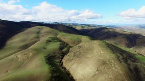Volo del fuco sopra le colline meravigliose e gli ampi campi stock footage