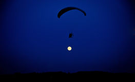 Volo del paracadutista contro la luna Fotografie Stock
