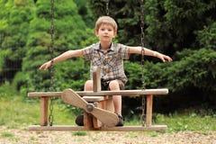 Volo del ragazzo su un'oscillazione di legno del biplano nel parco di estate Esaminando la macchina fotografica Fotografie Stock