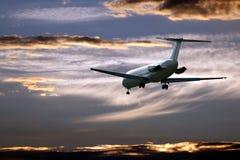 Volo dell'æreo a reazione di aereo di linea nel cielo di sera al tramonto Fotografie Stock Libere da Diritti