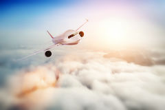 Volo dell'aeroplano del passeggero al tramonto, cielo blu Immagini Stock