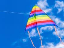 Volo dell'aquilone del vento in un cielo blu Immagini Stock Libere da Diritti