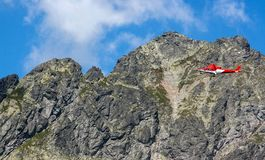Volo dell'elicottero di salvataggio nelle montagne rocciose immagini stock