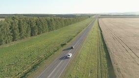 Volo dell'elicottero sopra l'automobile nel campo e sulla strada principale archivi video