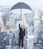Volo dell'uomo d'affari con l'ombrello sopra la città co di megapolis di sera Fotografia Stock