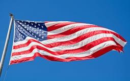 Volo della bandiera americana in cielo blu luminoso Immagini Stock