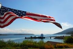 Volo della bandiera americana sopra il lago Fotografia Stock