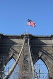 Bandiera americana sopra il ponte di Brooklyn famoso Fotografia Stock