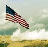 Volo della bandiera americana sopra la sommità con le nubi Fotografie Stock