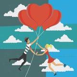Volo della donna e dell'uomo con i palloni di amore Fotografia Stock