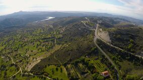 Volo della macchina fotografica sopra le colline verdi maestose con di olivo, montagne sull'orizzonte video d archivio