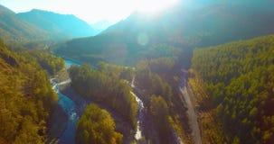 Volo della metà di aria sopra il fiume ed il prato freschi della montagna alla mattina soleggiata di estate Strada non asfaltata  stock footage