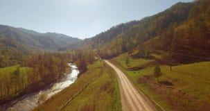 Volo della metà di aria sopra il fiume ed il prato freschi della montagna alla mattina soleggiata di estate Strada non asfaltata  archivi video