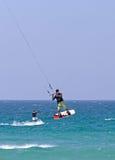 Volo di Kitesurfer attraverso l'aria su una spiaggia piena di sole fotografia stock