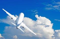 Volo di salita degli aerei contro lo sfondo dei cumuli Fotografie Stock