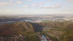 Volo di vista aerea sopra un fiume con il ponte, città moderna archivi video