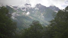 Volo dopo le montagne nevose nelle nuvole archivi video