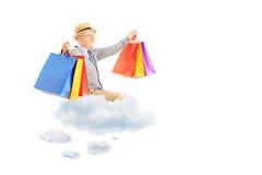 Volo felice dell'uomo senior sulle nuvole e sui sacchetti della spesa della tenuta Fotografia Stock Libera da Diritti