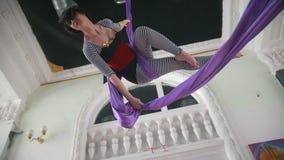 Volo flessibile attraente della ginnasta dell'aria della donna sulla seta aerea video d archivio