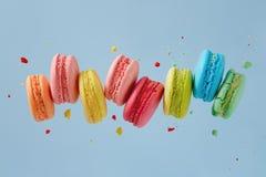 Volo Macarons sul fondo blu fotografia stock