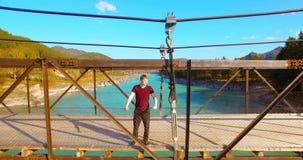 Volo mezz'aria sopra il turista del giovane che resta attraverso un ponte sospeso video d archivio