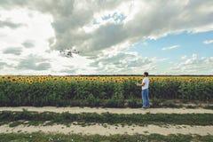 Volo professionale del fuco con il fondo del cielo blu controllato dal giovane Fotografia Stock