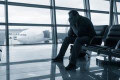 Volo in ritardo aspettante dell'uomo triste Immagine Stock