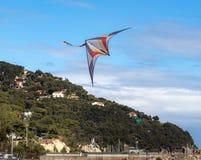 Volo rosso e bianco dell'aquilone in cielo blu con nuvoloso nell'Andora, Italia fotografie stock