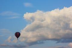 Volo solo del baloon dell'aria davanti alle nuvole gonfie bianche immagine stock
