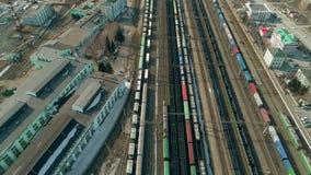 Volo sopra il treno del carico che si muove dopo la vista della stazione ferroviaria dalla cima stock footage