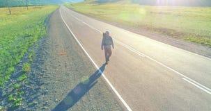 Volo sopra il turista dell'autostoppista che cammina sulla strada asfaltata Valle rurale enorme al giorno di estate Zaino che fa  video d archivio