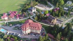 Volo sopra il villaggio nelle montagne ucraine di Carpathians Grande vista aerea di Pylypets dell'hotel stock footage
