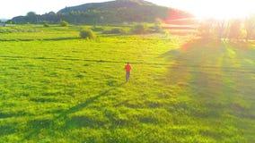 Volo sopra l'uomo di sport al prato perfetto dell'erba verde Tramonto in montagna stock footage