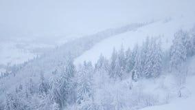 Volo sopra la bufera di neve in una montagna nevosa, tempo poco amichevole scomodo di inverno archivi video