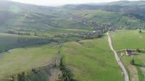 Volo sopra la foresta nelle montagne e nel villaggio Vista aerea di ucranino Carpathians stock footage