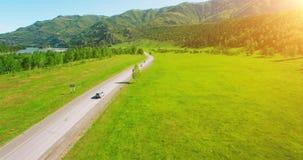 Volo sopra le automobili su una strada di bobina nelle colline e nel prato Strada principale rurale qui sotto video d archivio