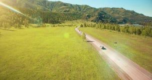 Volo sopra le automobili su una strada di bobina nelle colline e nel prato Strada principale rurale qui sotto archivi video