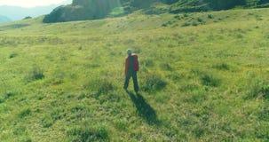 Volo sopra lo zaino che fa un'escursione turista che cammina attraverso il giacimento verde della montagna Valle rurale enorme al archivi video