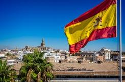 Volo spagnolo della bandiera con la cattedrale di Siviglia nei precedenti in Siviglia, Spagna fotografie stock libere da diritti