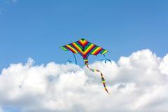 Volo variopinto dell'aquilone in un cielo blu con le nuvole Fotografia Stock