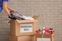 Volontären som samlar kläder in i donation, boxas fotografering för bildbyråer