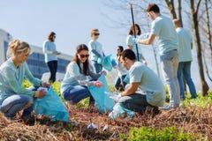Volontärer med att göra ren för avskrädepåsar parkerar område royaltyfri foto
