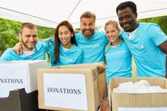Volontärer med donationaskar är lyckliga fotografering för bildbyråer