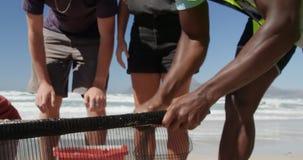 Volontärer som gör ren stranden på en solig dag 4k arkivfilmer