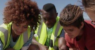 Volontärer som gör ren stranden på en solig dag 4k lager videofilmer